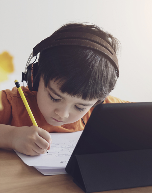 Photo of young boy wearing headphones and writing