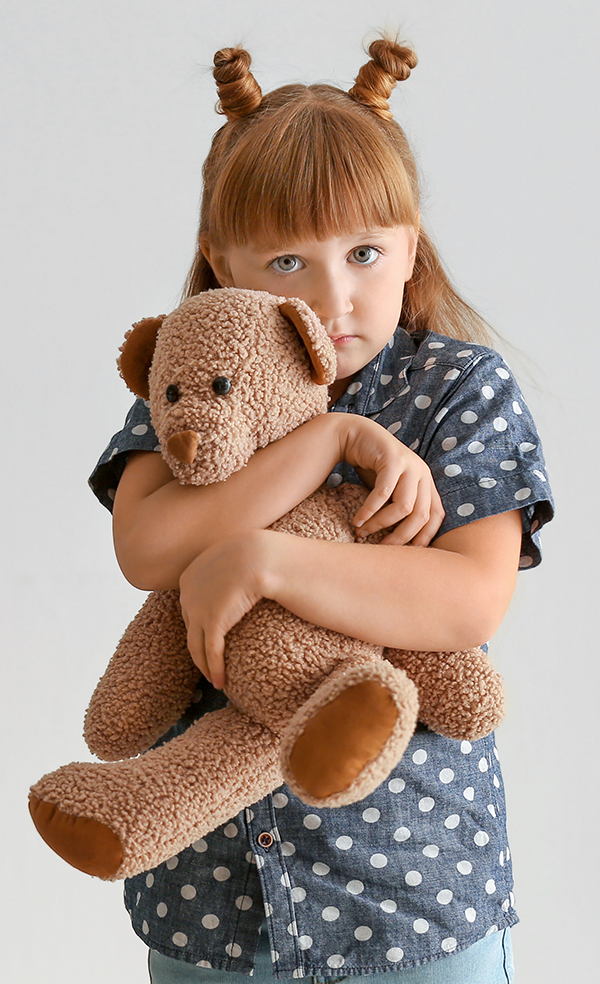Photo of young girl holding teddy bear