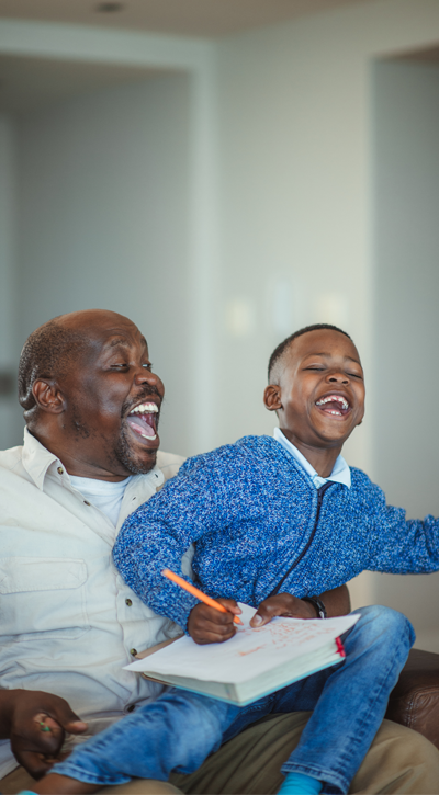Photo of father and son laughing over a book.